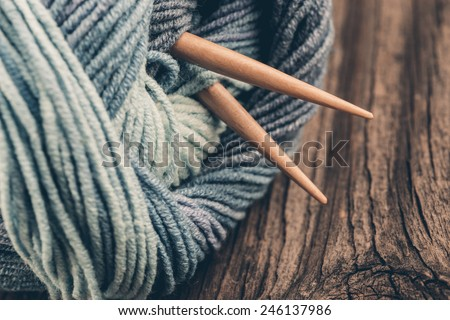 Knitting needles and yarn on wooden background/natural wool knitting background - stock photo
