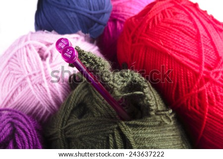 Knitting needles with the start of a garment and balls of colorful wool in charcoal grey, red, lilac and blue, closeup background texture - stock photo