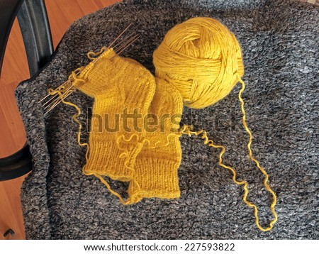 Knitting socks and yellow yarn ball on office chair - stock photo