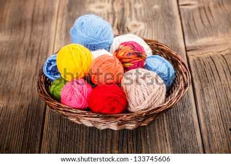 Knitting yarn in basket on rustic wooden background - stock photo