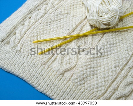 Knitwear in Aran cables of an Irish sweater with knitting needles and a ball of wool