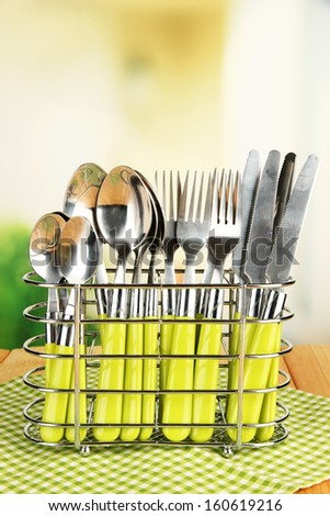 Knives, forks and spoons in metal stand on table on bright background - stock photo