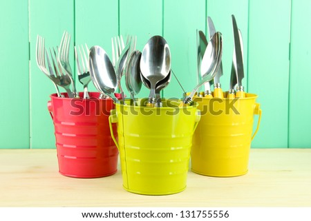 Knives, spoons, forks in colorful buckets on color wooden background - stock photo