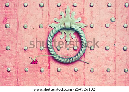 Knocker on a red medieval wooden door with a rose placed in it with a vintage filter applied - stock photo