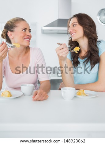 Knowing women eating cake and having coffee together in the kitchen - stock photo
