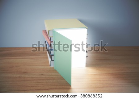 Knowledge concept with opened book with glowing pages and pile of books behind on wooden table - stock photo