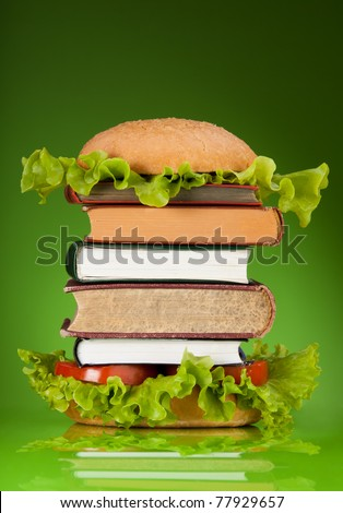 Knowledge fast food concept represented by burger with books on green background - stock photo