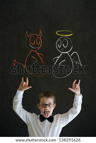 Knowledge rocks boy dressed up as business man with chalk angel and devil on shoulder making decision on blackboard background - stock photo
