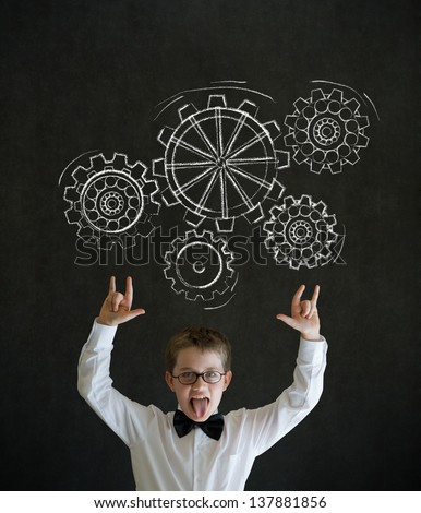 Knowledge rocks boy dressed up as business man with chalk turning gear cogs or gears on blackboard background - stock photo