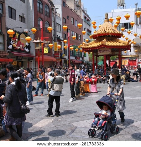 KOBE, JAPAN - APRIL 24, 2012: Visitors enjoy sunny weather in Chinatown in Kobe, Japan. Nankinmachi, Kobe's Chinatown is the 2nd largest in Japan and a popular tourism attraction. - stock photo