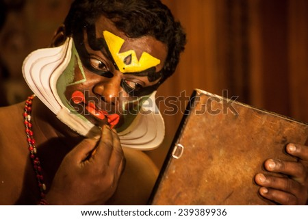 KOCHI, INDIA - DECEMBER 7 , 2012: Unidentified Kathakali exponent preparing for performance by applying face make-up on December 7, 2012 / Kathakali is the classical dance form of Kerala