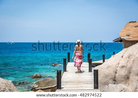 Koh Tao, Thailand - June 20th. 2016 - Young woman in front of a tropical clear sea in Koh Tao island in Thailand, Asia.