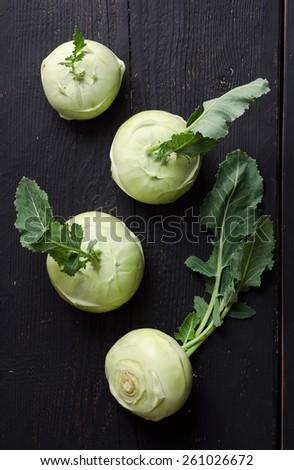 Kohlrabi or french turnips over black wooden table - stock photo