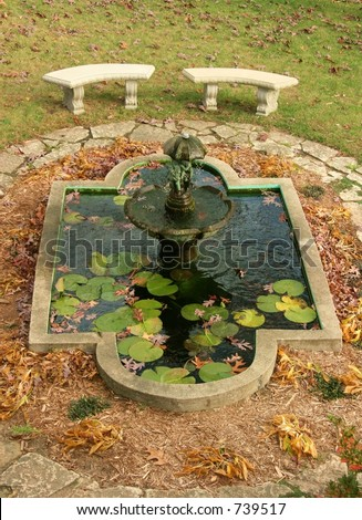 Koi pond with benches and bronze fountain, surrounded by fall leaves. - stock photo