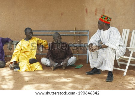 KOKEMNOURE, BURKINA FASO - FEBRUARY 23: The village chief Kokemnoure Andre Silga talks with villagers come to greet him and maybe ask him his opinion on questions of a private, february 23, 2007.  - stock photo