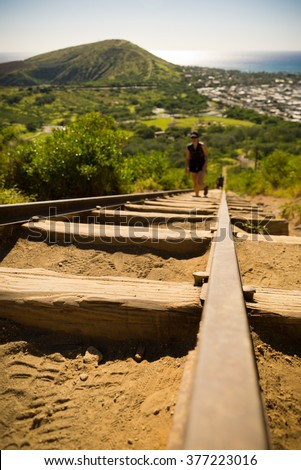Koko Head's Crater and hikers attempting to climb its 1048 steps on a sunny day across from Hanauma Bay in the south east coast of Oahu outside Honolulu - stock photo