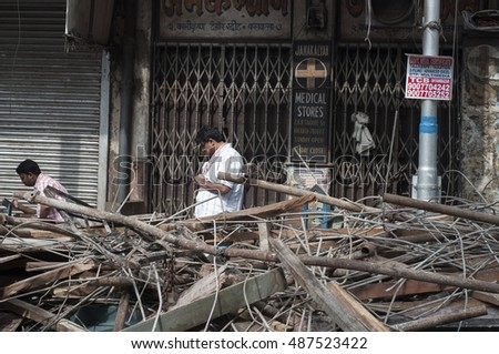 KOLKATA - APRIL 1: A man checks his cell phone in front of the rubble during the rescue effort after an under construction flyover collapsed killing 27 people on April 1, 2016 in Kolkata, India.