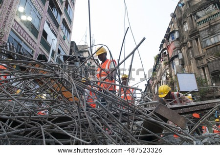 KOLKATA - APRIL 1: Rescue workers cleaning up concrete during the rescue effort after an under construction flyover collapsed killing 27 people on April 1, 2016 in Kolkata, India.