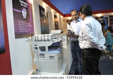 KOLKATA- FEBRUARY 20: A customer asking questions about a  photocopier, during the Information and Communication Technology (ICT) conference and exhibition in Kolkata, India on February 20, 2011. - stock photo