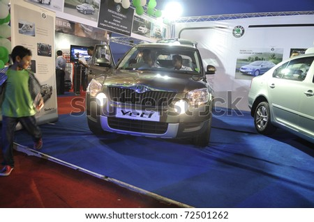 KOLKATA- FEBRUARY 20: A kid runs away as his family starts the engine of a Skoda van,during the Information and Communication Technology conference and exhibition in Kolkata,India on February 20,2011.