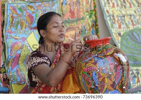 KOLKATA - FEBRUARY 23: A rural woman painting a pot during  Handicraft Fairin Kolkata -the biggest of its kind in Asia, on February 23, 2011 in Kolkata, India. - stock photo