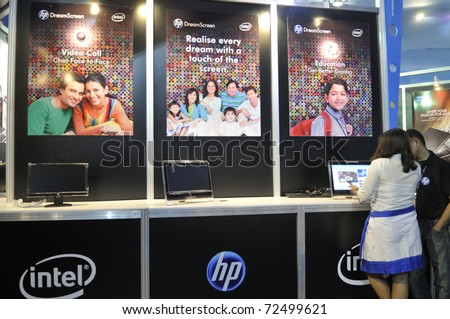 KOLKATA- FEBRUARY 20:A sales associate explaining customers about HP products during the Information and Communication Technology (ICT) conference and exhibition in Kolkata, India on February 20,2011. - stock photo