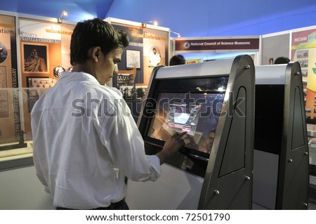 KOLKATA- FEBRUARY 20: A  young man operates a touch screen, during the Information and Communication Technology (ICT) conference and exhibition in Kolkata, India on February 20, 2011. - stock photo