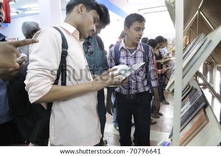 KOLKATA- FEBRUARY 4: Young Bengali adults go through books of their choices during the 2011 Kolkata Book Fair in Kolkata, India on February 4, 2011. - stock photo