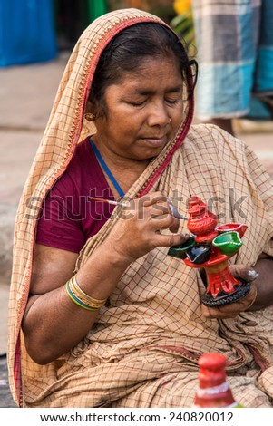 KOLKATA, INDIA - DECEMBER 11: An Indian craftswoman creates colorful handicraft items for sale during the annual State Handicrafts Expo 2014 on December 11, 2014 in Kolkata, West Bengal, India. - stock photo