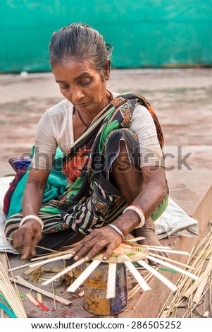 KOLKATA, INDIA - DECEMBER 11: An Indian craftswoman weaves a cane basket for sale during the annual State Handicrafts Expo 2014 on December 11, 2014 in Kolkata, West Bengal, India. - stock photo