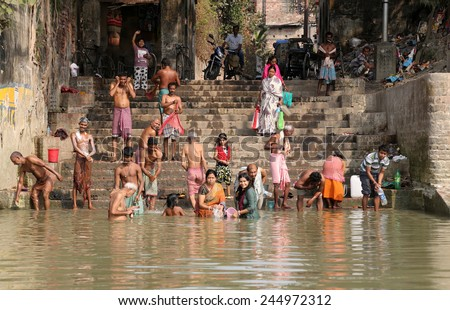 KOLKATA, INDIA - FEB 14: Hindu people bathing in the ghat near the Dakshineswar Kali Temple on February 14, 2014. At present time this river is being polluted tremendously. - stock photo
