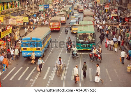 KOLKATA, INDIA - JAN 20: Crossroad of busy modern city in Asia with cars, bikes, walking people and buses on January 20, 2016 in Calcutta. Kolkata has a density of 814.80 vehicles per km road length - stock photo