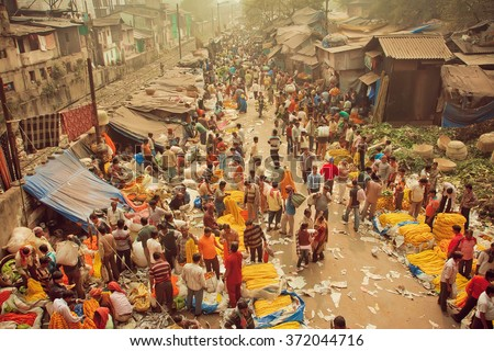 KOLKATA, INDIA - JAN 13: Crowd of busy people buying flowers at Mullik Ghat Flower Market on indian street on January 13, 2016. More than 125 years old market has near 2000 sellers workers every day - stock photo