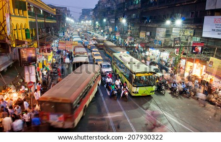 KOLKATA, INDIA - JAN 22: Dark city traffic blurred in motion at late evening on crowded streets on January 22, 2013 in Calcutta. Kolkata has a density of 814.80 vehicles per km road length  - stock photo