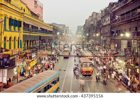 KOLKATA, INDIA - JAN 17: Huge city with traffic scene and colorful buildings in business district with moving buses on January 17, 2016. Kolkata has a density of 814.80 vehicles per km road length - stock photo