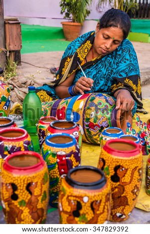 KOLKATA, INDIA - NOVEMBER 24: An Indian craftswoman paints on colorful handicraft items for sale during the annual State Handicrafts Expo 2015 on November 24, 2015 in Kolkata, West Bengal, India. - stock photo
