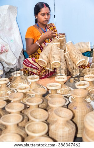 KOLKATA, INDIA - NOVEMBER 24: An Indian craftswoman weaves cane items for sale during the annual State Handicrafts Expo 2015 on November 24, 2015 in Kolkata, West Bengal, India. - stock photo