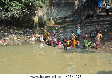 KOLKATA, INDIA -OCTOBER 27: A group of Indian people wash themselves in Hooghly River on October 27, 2009. At present time this river is being polluted tremendously. - stock photo