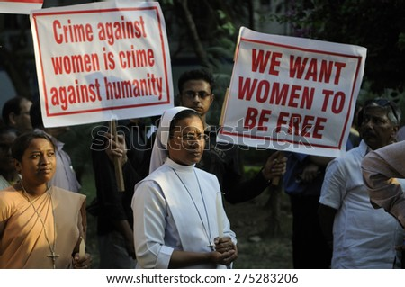 KOLKATA - MARCH 16 : A Christian Nun standing in prayer during a candle light vigil to protest gang rape of an elderly nun near Ranaghat on March 16, 2015 at Allen Park in Kolkata, India. - stock photo