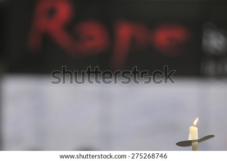 KOLKATA - MARCH 16 : A protester holding a burning candle during a candle light vigil to protest gang rape of an elderly nun on March 16, 2015, at Allen Park in Kolkata, India.