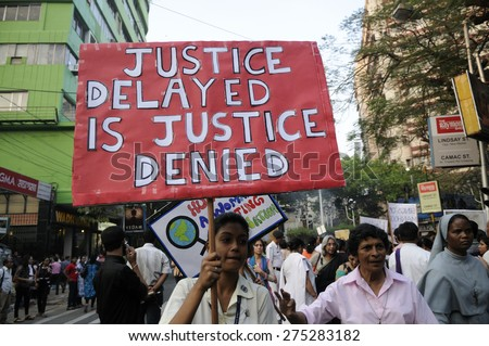 """KOLKATA - MARCH 16 :A school girl carrying a message saying """"justice delayed is justice denied"""" during a candle light vigil to protest gang rape of an elderly nun on March 16, 2015  in Kolkata, India. - stock photo"""