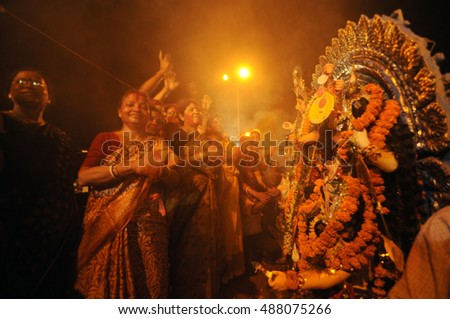 KOLKATA - OCT 17: Devotees dance in front of huge Durga idol before immersion during Durga Puja festival on October 17, 2010 in Kolkata, India. Durga puja is the biggest festival in West Bengal, India