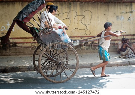 KOLKATA -OCT 06: Traditional hand pulled indian rickshaw driver working on the street on October 10, 2014 in Kolkata, India.  - stock photo