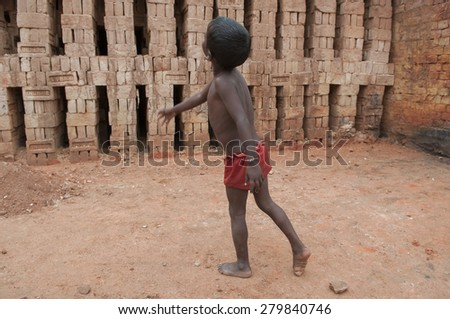 KOLKATA - OCTOBER 26 : A small boy playing  inside a brick factory where his parents stay and work under inhuman conditions at times on October 26, 2014 in Kolkata , India. - stock photo