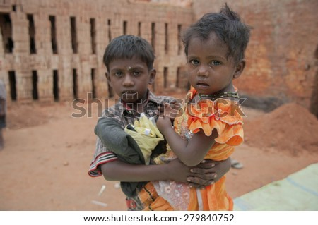 KOLKATA - OCTOBER 26 : Elder brother carrying his sister inside a brick factory   where their parents stay and work under inhuman conditions at times on October 26, 2014 in Kolkata , India. - stock photo