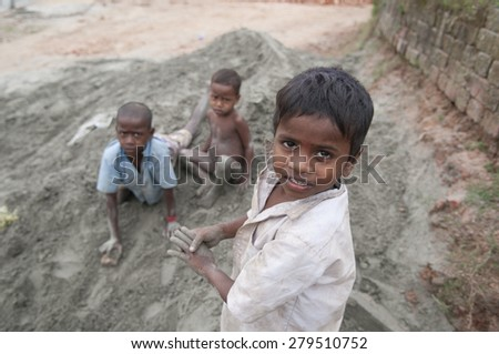 KOLKATA -OCTOBER 26 :Kids playing on clay later to be used for brick manufacturing- an industry in India where families work under terrible conditions on October 26, 2014 in Kolkata,India.  - stock photo