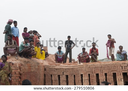 KOLKATA - OCTOBER 26 : Workers and their family members  inside a brick factory where they work and stay under tough and unhealthy conditions on October 26, 2014 in Kolkata , India.  - stock photo