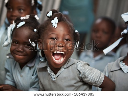 KOLMINY, HAITI - FEBRUARY 12, 2014 - Adorable Haitian school girl in her classroom laughing.