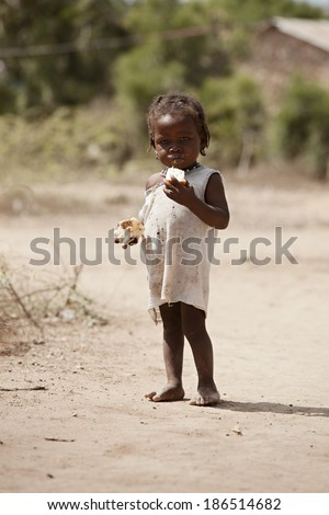 KOLMINY, HAITI - FEBRUARY 12, 2014. Undernourished Haitian child eating some peanut butter bread given to her by missionaries. - stock photo