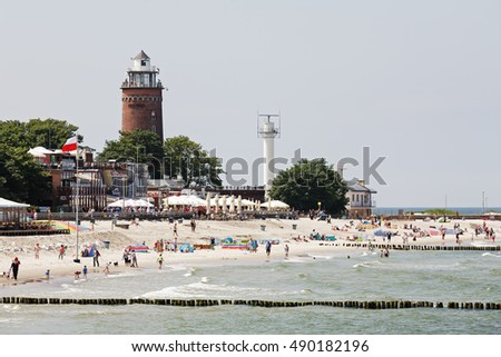 KOLOBRZEG, POLAND - JUNE 19, 2016: Massive lighthouse by the sandy beach where many vacationers can be seen